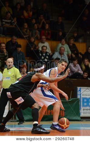 KAPOSVAR, HUNGARY - JANUARY 21: Gergely Kutasi (in white) in action at a Hungarian Championship basketball game with Kaposvar (white) vs. Szolnok (black) on January 21, 2012 in Kaposvar, Hungary.
