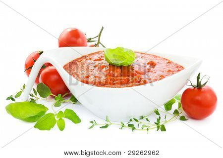 Sauce boat with fresh tomato sauce with herbs and tomatoes on a white background