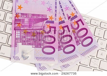500 euro banknotes are a lot of money on a pile. On a computer keyboard