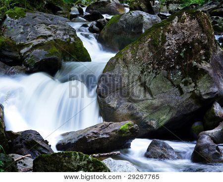 arroyo con agua y piedras en las montañas.