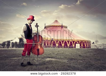Young man in funny clothes holding a cello with circus in the background