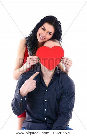 A beautiful young woman hides her face behind a guy with a big red heart
