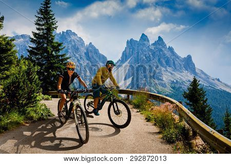 poster of Couple cycling on electric bikes. Woman and Man riding on bikes in Dolomites mountains landscape. Cy