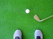 Golf Ball And Iron Golf Club With Golfer Standing On Synthetic Artificial Turf In Driving Range poster