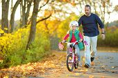 Happy Father Teaching His Little Daughter To Ride A Bicycle. Child Learning To Ride A Bike On Sunny  poster