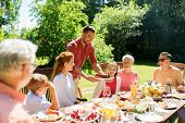 leisure, holidays and people concept - happy family having festive dinner or barbecue party at summe poster