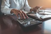 Woman With Bills And Calculator. Woman Using Calculator To Calculate Bills At The Table In Office. C poster