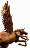 image of chainsaw  - Chainsaw sculpture of a wooden Pegasus unicorn taking flight isolated on white - JPG