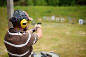 Man Shooting On An Outdoor Shooting Range. Male Aiming Gun At Firing Range. poster