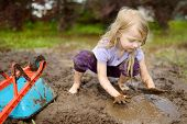 Funny Little Girl Playing In A Large Wet Mud Puddle On Sunny Summer Day. Child Getting Dirty While D poster