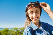 Portrait Of A Young Smiling Attractive Woman With Sunglasses At Sunny Day On The Blue Sky Background poster