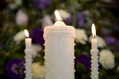 stock photo of unity candle  - wedding unity candles lit with purple background flowers - JPG
