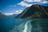 Waves Behind A Cruise Ship On A Magnificent Fjord In Norway. Sunny Day . Emerald Waters Of The Fjord poster