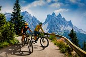 Couple cycling on electric bikes. Woman and Man riding on bikes in Dolomites mountains landscape. Cy poster