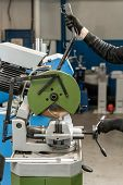 Worker Cuts A Piece Of Material With A Circular Saw Machine. Industrial Engineer Working On Cutting  poster