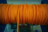 The Orange Rope Is Reeled Up On The Coil In Shop. A Saving Or Safety Rope For Climbers. Texture Of A poster