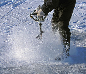 stock photo of ice fishing  - drilling a hole through the ice with an auger - JPG