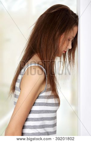 Site view of a young female teen being depressed, resting her head on a wall, on white.