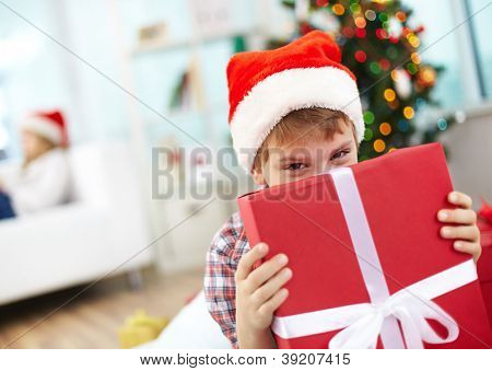 Portrait of cheerful boy peeking out of big red giftbox on Christmas evening