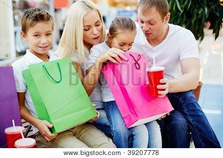 Retrato de família alegre ter ruptura e procura pelo paperbags no shopping