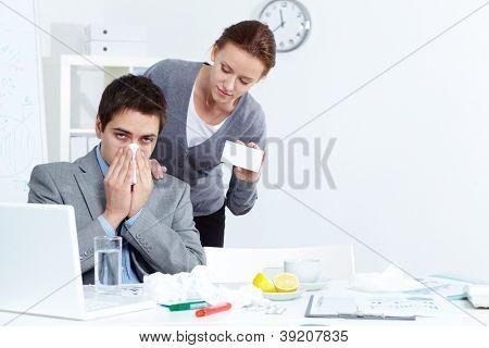 Imagem do empresário doente com lenço, olhando para a câmera enquanto seu parceiro, oferecendo-lhe bom med