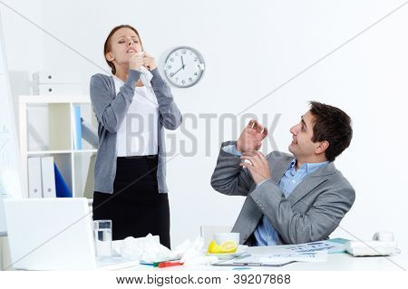 Image of sick businesswoman sneezing while her partner looking at her with anxiety in office