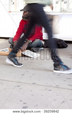 NEW YORK - OCT 18: A homeless man in Times Square sits on the sidewalk with a sign that reads 'Please Help' as people walk by in New York City on October 18, 2012.