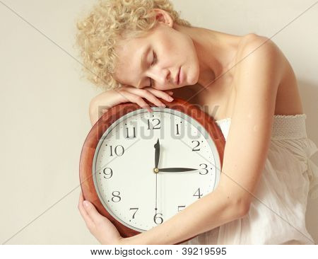 Young scrawny girl with big clock in hands