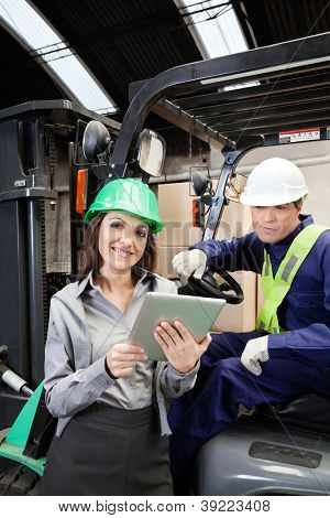 Portrait of female supervisor and forklift driver with digital tablet at warehouse
