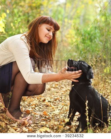 Teenager Girl With Black Labrador Retriever Puppy