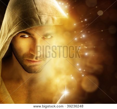 Fantastical portrait of a handsome hero type man in hooded garment in dazzling background with rays of light
