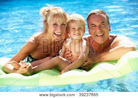 Grandparents And Grandson Having Fun In Swimming Pool