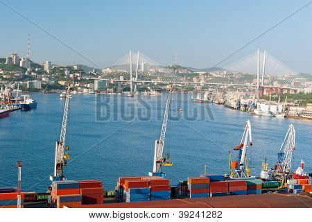 container terminal at russian port Vladivostok against the downtown and new bridge over Golden Horn bay
