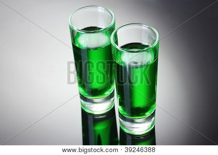 Two glasses of absinthe on grey background