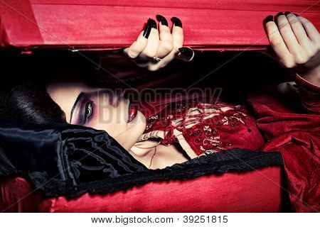 Bloodthirsty female vampire rises from the coffin on the night cemetery.