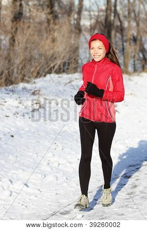 Winter snow runner woman running outside on cold winter day smiling happy. Fit healthy lifestyle concept with beautiful young fitness model. Mixed race Asian / Caucasian jogging outside in full length