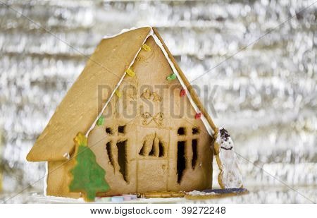 Cute gingerbread house on silver background