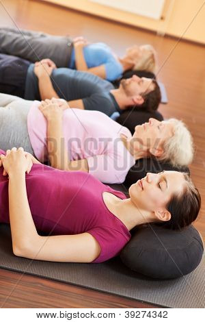 Mixed group in yoga class relaxing in a fitness center