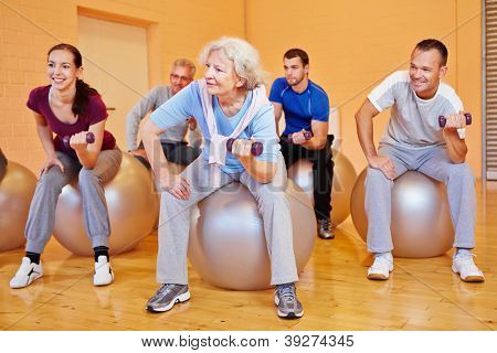 Happy group doing back training exercises in gym with dumbbells
