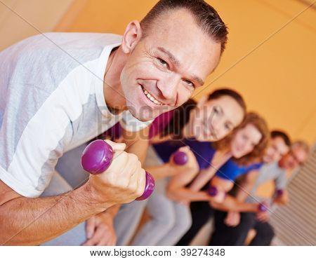 Happy best ager man in fitness center lifting dumbbells