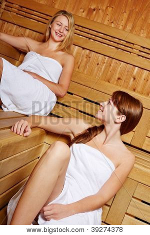 Two smiling women talking in a sauna