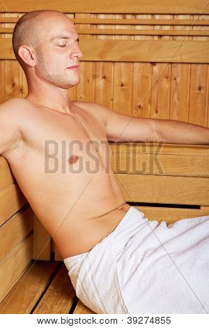 Attractive man resting in a sauna and relaxing