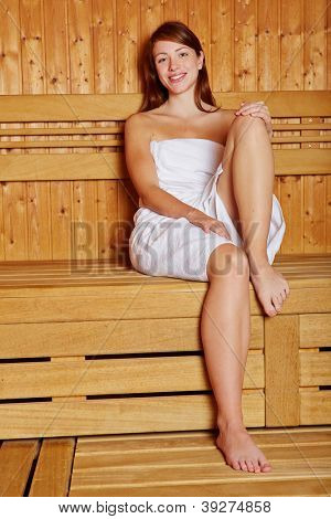 Attractive woman sitting smiling in a sauna