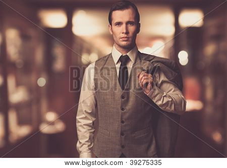 Man in waistcoat with jacket over his shoulder against blurred background
