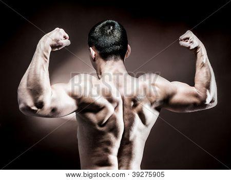 muscular male back on dark background