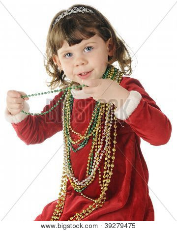 An adorable preschooler in her red velvet Christmas dress happily wearing oodles of Christmas beads.  On a white background.