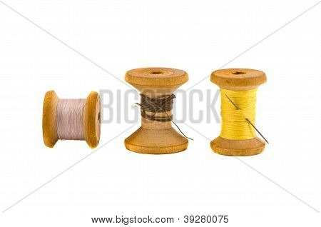 Three Old Thread Spools On White