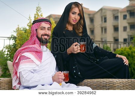 Arabian couple relaxing in the garden and drinking tea