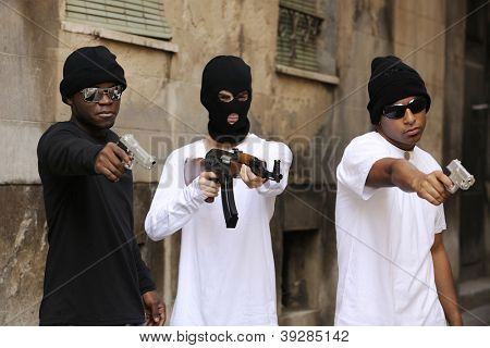 Gang members or guerrilla with gun and rifle on the street