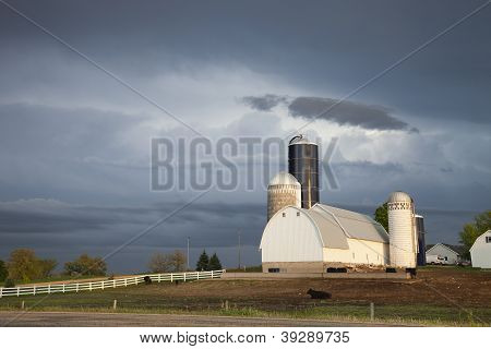 Barn And Silos Of Midwestern Farm Under Stormy Skies